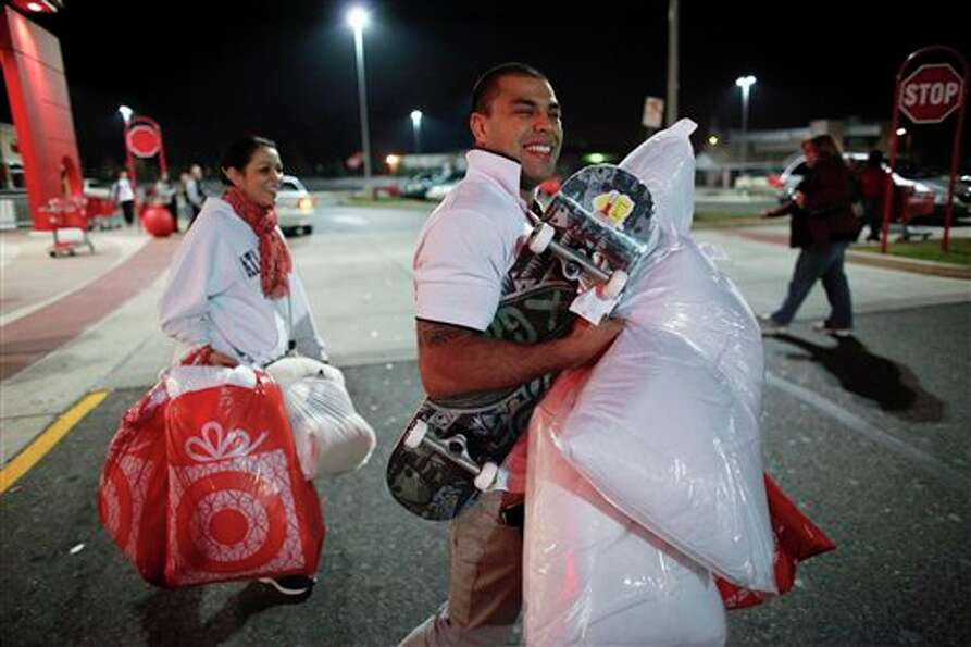 Rafael Pinguim, right, and Johanna Santos carry their purchases after shopping for Black Friday disc