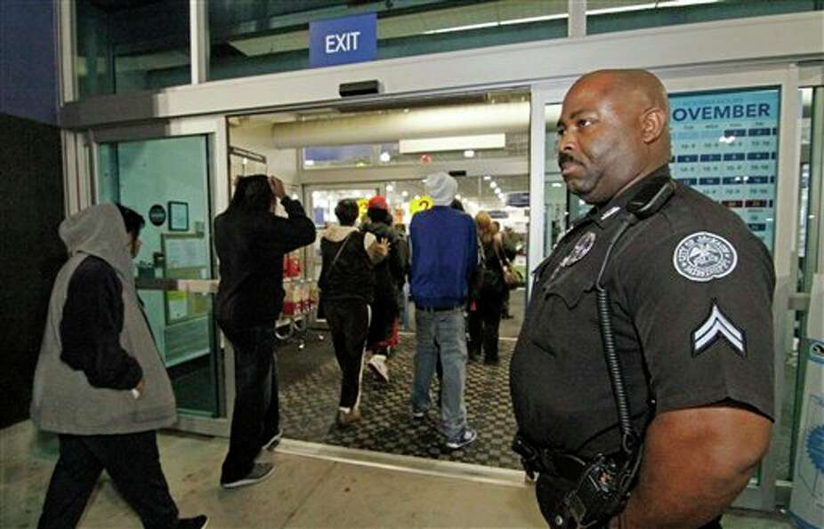 Jackson Police Cpl. Terry Hopkins Sr. watches customers enter Best Buy in Jackson, Miss., for the ea