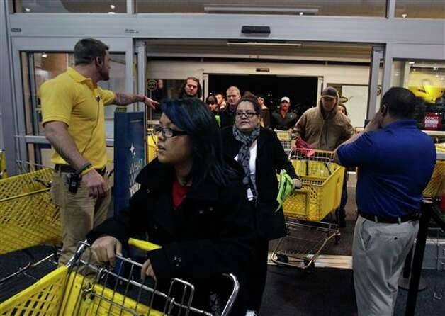 Best Buy electronics store employees, at far right and left, open doors to shoppers for a Black Friday sale that began at midnight, in Broomfield, Colo., early Friday Nov. 23, 2012. Photo: Brennan Linsley, AP / AP2012