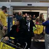 Best Buy electronics store employees, at far right and left, open doors to shoppers for a Black Friday sale that began at midnight, in Broomfield, Colo., early Friday Nov. 23, 2012.