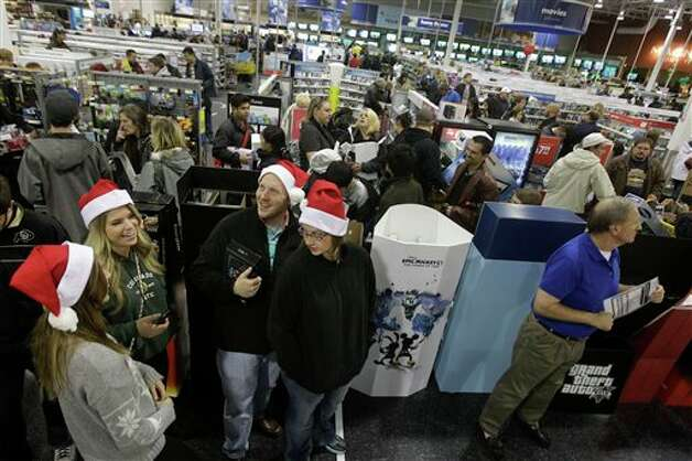 Shoppers, at bottom, right to left, Karin Carlson, of Wichita, Kan., her husband Jason, and her cousins Tylar Neu and Christie LaFever wait in line to pay for items for purchase at Best Buy electronics store, after doors opened for a Black Friday sale that started at midnight, in Broomfield, Colo., early Friday Nov. 23, 2012. Photo: Brennan Linsley, AP / AP2012