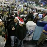 Shoppers, at bottom, right to left, Karin Carlson, of Wichita, Kan., her husband Jason, and her cousins Tylar Neu and Christie LaFever wait in line to pay for items for purchase at Best Buy electronics store, after doors opened for a Black Friday sale that started at midnight, in Broomfield, Colo., early Friday Nov. 23, 2012.