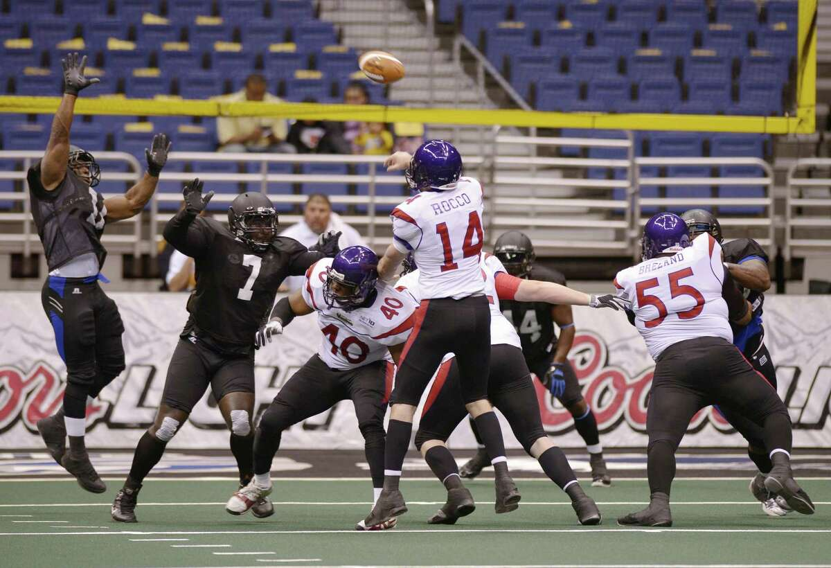 New Orleans Voodoo quarterback Kurt Rocco (14) passes over San Antonio Talons' DJ Stephens (7) and Joe Sykes during an arena football game, Wednesday, March 6, 2013, at the Alamodome in San Antonio. (Darren Abate/For the Express-News)