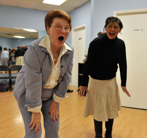 Jo Stier (left) and Hildi Mayorga let out a laugh during an execise in the Laughter Yoga  class recently. The exercises are designed to relieve stress and improve health. Photo: Robin Jerstad, For The Express-News