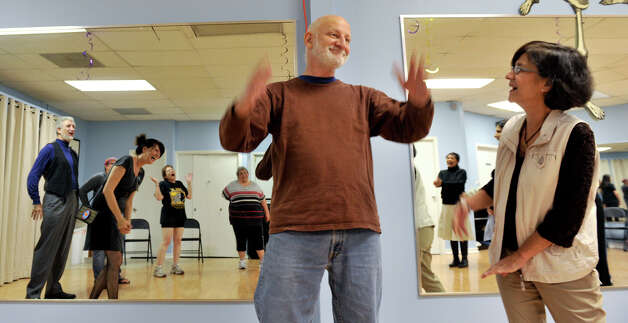 Tom Mandelbaum and Lupe Braid do laugh during an exercise in the Laughter Yoga class reently. Photo: Robin Jerstad, For The Express-News