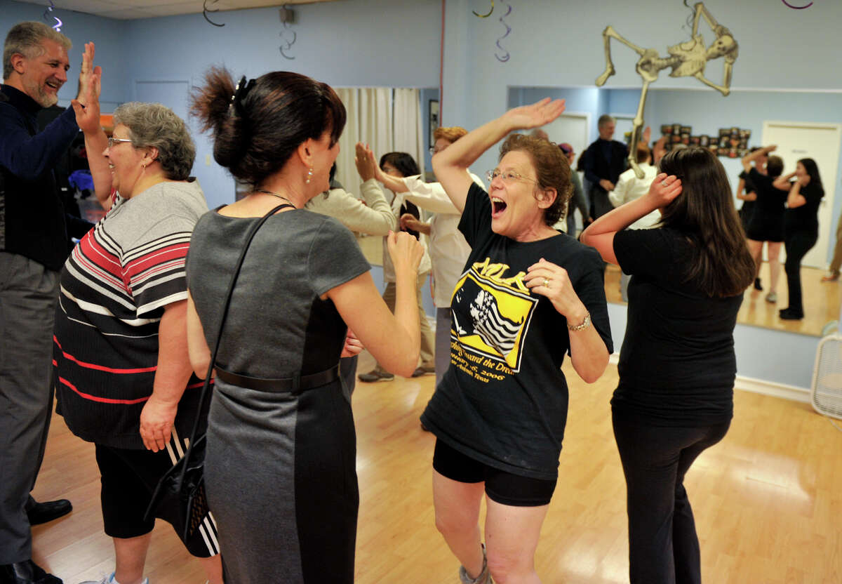 Laughter Yoga participant Marianne Kesterbaum high-fives certified Laughter Yoga leader Ruthie Premack during a class exercise.
