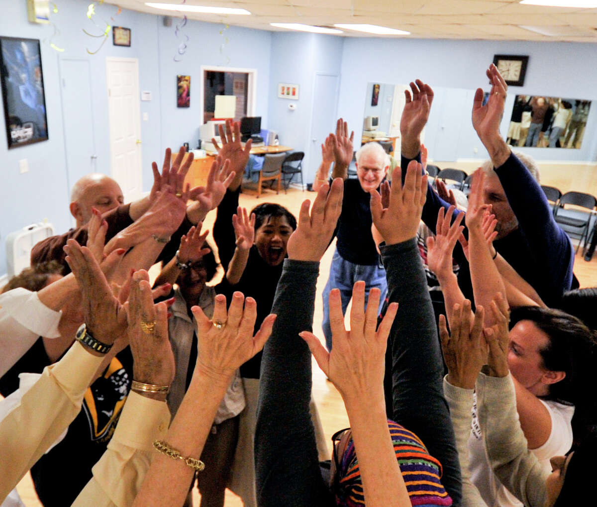 Members of the Laughter Yoga Club high-five each other during an exercise recently.