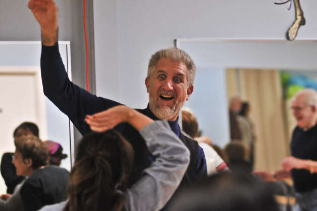 Paul Premack does an exercise during a Laughter Yoga class, which is to help relieve stress and improve health. Photo: Robin Jerstad, For The Express-News
