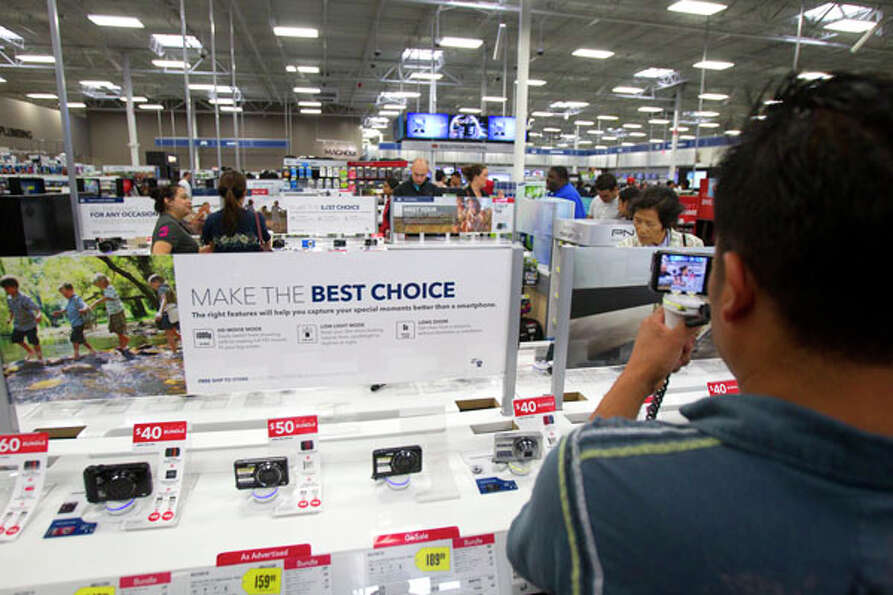 Gaspar Tecum looks at a camera at Best Buy during Black Friday, Nov. 23, 2012, in Houston.
