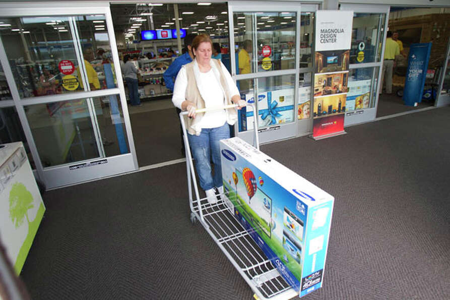 Barbara Coffey rolls a TV out of Best Buy during Black Friday, Nov. 23, 2012, in Houston.