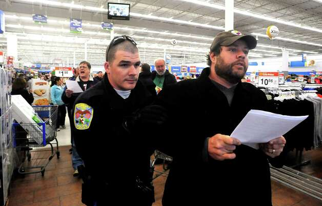 Danbury police remove protesters, including Joe Hill, right, from Walmart during a demonstration Friday, Nov. 23, 2012. Photo: Michael Duffy / The News-Times