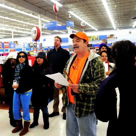 Prosters including John Woodruff, right center, chant inside Walmart in Danbury during a demonstration Friday, Nov. 23, 2012. Photo: Michael Duffy / The News-Times