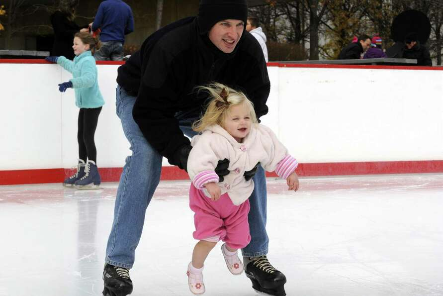 Nate Henderson holds his one-year-old daughter Hadley Henderson as he skates at the Empire State Pla