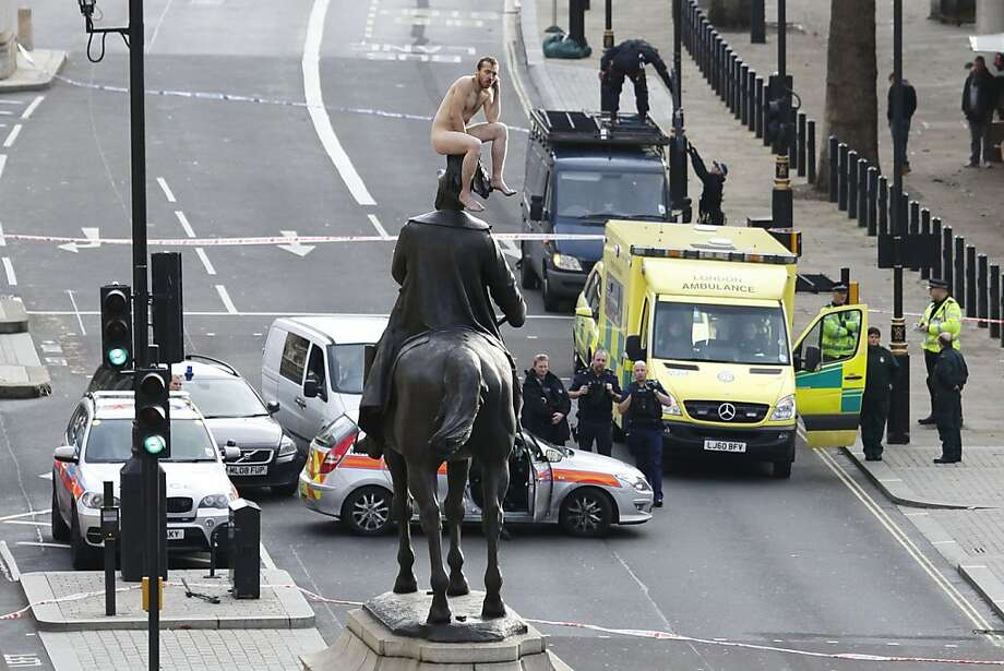 "A naked Britbesmirches the memory of Prince George, Duke of Cambridge, by setting his commoner cheeks on the royal head in London. The unidentified man, who brought Whitehall to a standstill for almost two hours, assumed various poses before being eventually talked down. This apparently is ""The Thinker."" Photo: Justin Tallis, AFP/Getty Images"