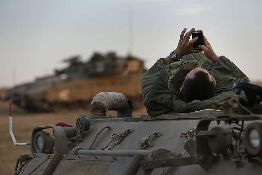 An Israeli soldier checks his cell phone after waking atop an armored personnel carrier at a staging area near Israel's Gaza Strip border on Wednesday, the day of the cease-fire. Photo: Lefteris Pitarakis, Associated Press