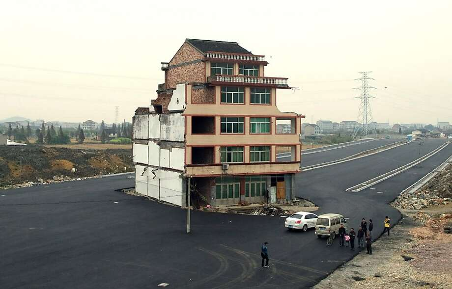 "This picture taken on November 22, 2012 shows a half-demolished apartment building standing in the middle of a newly-built road thanks to a Chinese couple that refused to move in Wenling, in eastern China's Zhejiang province. Luo Baogen, 67, and his 65-year-old wife have waged a four-year battle to receive more than the 41,300 USD compensation offered by the local government of Daxi, a Chinese newspaper said.  The phenomenon is called a ""nail house"" in China, as such buildings stick out and are difficult to remove, like a stubborn nail. Photo: Str, AFP/Getty Images"