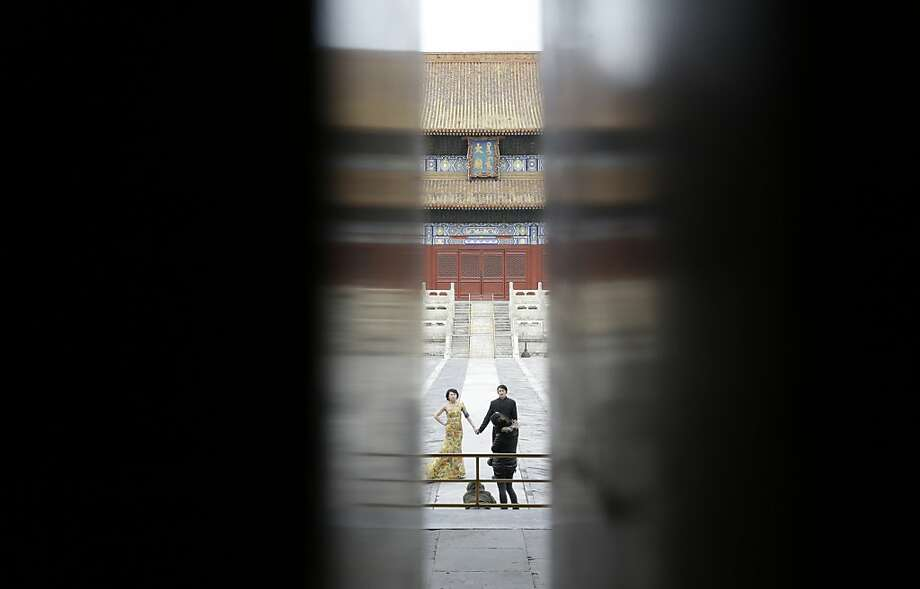 Seen through a gapbetween doors, a Chinese couple pose for their wedding pictures at the Imperial Ancestral Temple in Beijing. Photo: Lee Jin-man, Associated Press