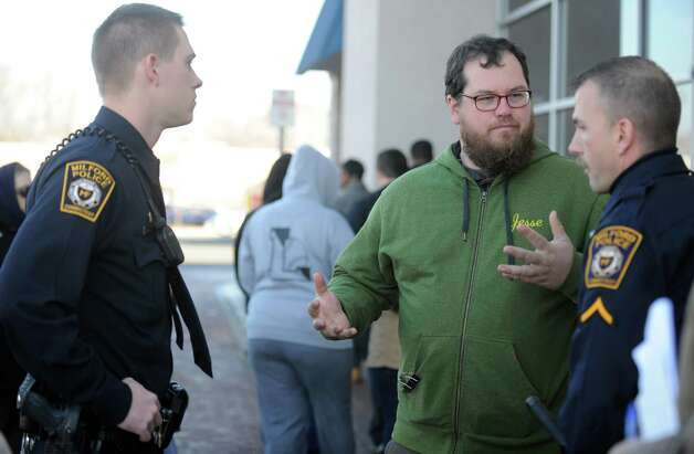 Local 1199 New England Health Care Employees Union representative Jesse Martin talks with police officers outside the Milford Walmart Friday, Nov. 23, 2012 as protesters march in support of improved benefits and compensation for Walmart workers.  The group was asked to move their rally off Walmart property. Photo: Autumn Driscoll / Connecticut Post