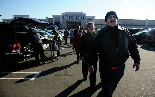 Phillip Bradeen, of West Haven, and other prosters rally outside the Milford Walmart Friday, Nov. 23, 2012 in support of improved benefits and compensation for Walmart workers. Photo: Autumn Driscoll / Connecticut Post