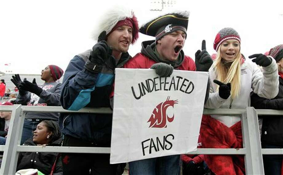 "Washington State fan Kyle Yeager, center, wears a pirate hat as he holds a sign that reads ""Undefeated Fans,"" as he cheers prior to the start. Photo: Ted S. Warren, AP / AP"