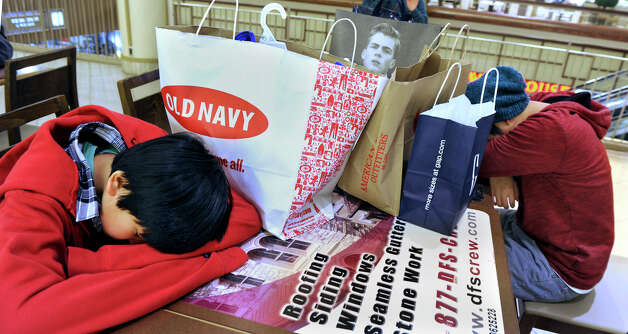 Johnathan Santayana, 16, left, and his brother E.J., 12, of Newtown, nap after a morning  shopping for Black Friday bargains at the Danbury Fair Mall. They arrived at the mall at about 2 a.m. after a midnight stop at Best Buy, Friday, Nov. 23, 2012. Photo: Carol Kaliff / The News-Times