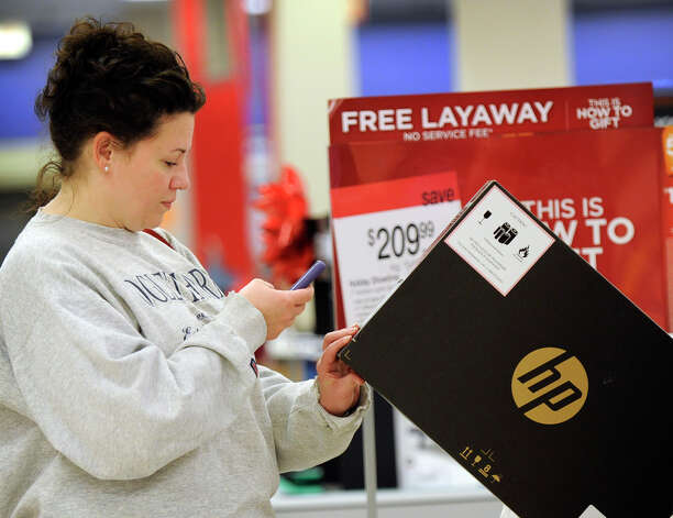Christie Blake, of Lunenburg, Mass., shopping at Sears with her sister-in-law, Stacey Moore of Danbury, uses her cellphone to check for the lowest prices, Black Friday, Nov. 23, 2012.  She determined she got the best deal available. Photo: Carol Kaliff / The News-Times