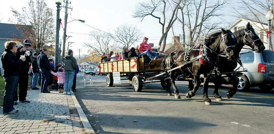 A horse-drawn carriage full with riders travels along Greenwood Avenue in Bethel as part of the holiday tree lighting festival. Friday, Nov. 23, 2012 Photo: Scott Mullin / The News-Times Freelance