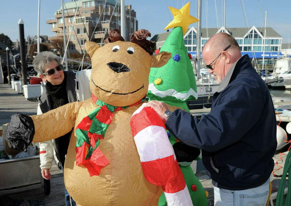 Andy Liljequist and his wife, Marty, decorate the lead boat for Saturday's Stamford Boat Parade in Stamford Harbor on Friday, November 23, 2012.