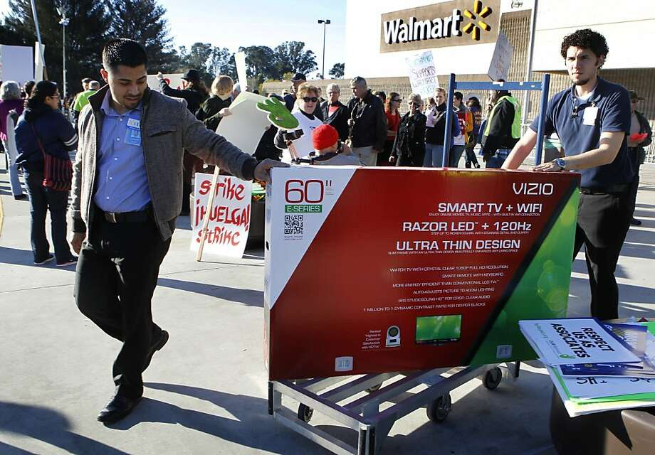 Unidentified employees deliver a television to a customer's car while demonstrators rally in front of the Walmart store in Richmond, Calif. on Friday, Nov. 23, 2012 to protest against poor working conditions and the termination of several employees. Photo: Paul Chinn, The Chronicle