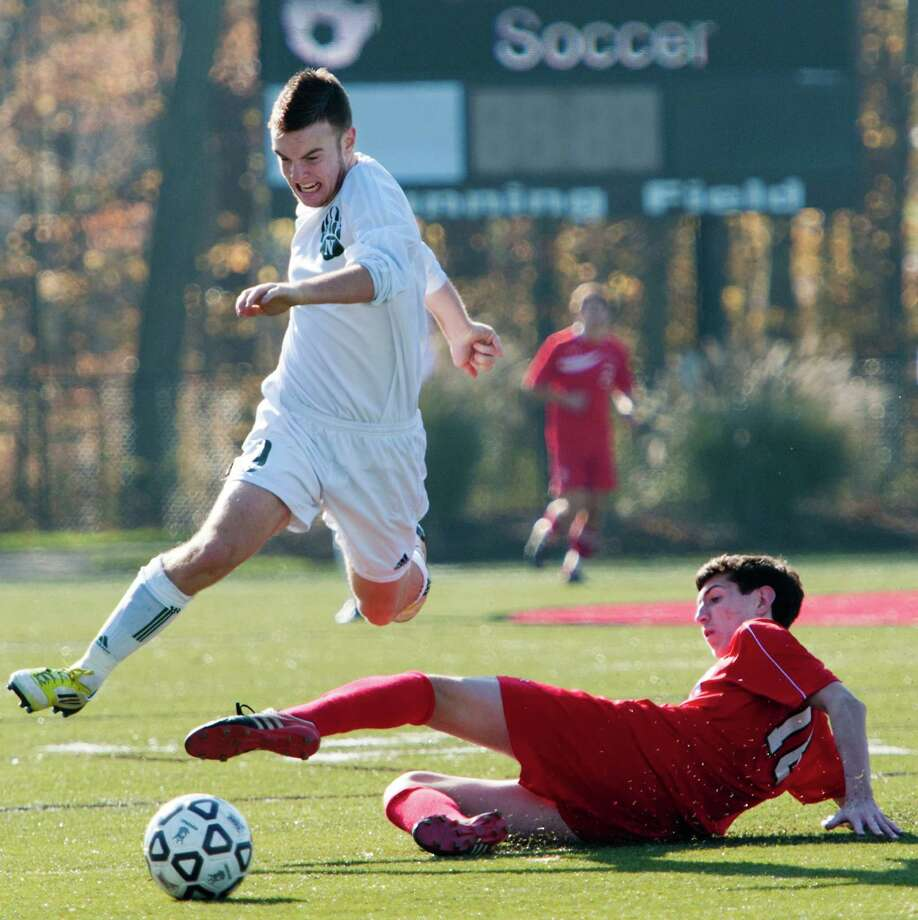 Norwalk high school's Kevin Joslyn leaps over Fairfield Prep high school's Jordan Visosky in the CIAC class LL boys soccer championship game held at New Canaan high school, New Canaan, CT on Friday November 23rd, 2012 Photo: Mark Conrad / Connecticut Post Freelance