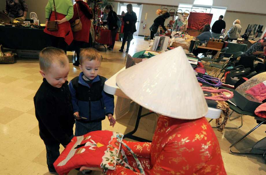 Two-year-old twin brothers Lincoln and McCann Whitney look at a handmade bag from Viet Nam imported by Ashley Allen, right, during a Black Friday fair trade market  at the Delmar Reformed Church in Delmar, NY Friday Nov. 23, 2012. The sale continues Saturday. (Michael P. Farrell/Times Union) Photo: Michael P. Farrell