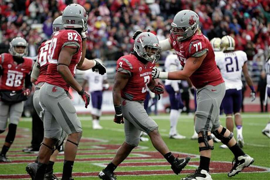 Washington State's Carl Winston (3) is greeted by teammate John Fullington (77) after scoring a touchdown against Washington in the first half. Photo: Ted S. Warren, AP / AP