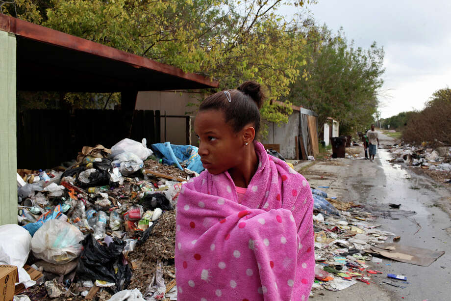 Nila Garrett, 13, watches as friends look for the source of running water behind a house they said was empty as they walk through an alley lined with trash and discarded furniture in Camelot II. They found an outside faucet running and turned it off. Photo: Lisa Krantz, San Antonio Express-News / © 2012 San Antonio Express-News