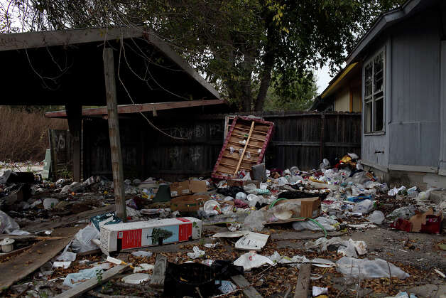 Trash and discarded furniture fills the backyard of an empty home along an alley in the Camelot II neighborhood in Northeast San Antonio on Friday, Nov. 23, 2012. Photo: Lisa Krantz, San Antonio Express-News / © 2012 San Antonio Express-News