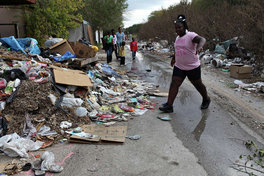Dejahnae Easterling, 9, walks through an alley lined with trash and discarded furniture in the Camelot II neighborhood in Northeast San Antonio on Friday, Nov. 23, 2012. Photo: Lisa Krantz, San Antonio Express-News / © 2012 San Antonio Express-News