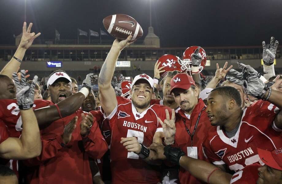 University of Houston QB Case Keenum, center, is among teammates celebrating a 73- 34 win over Rice University at Robertson Stadium Thursday, Oct. 27, 2011. (Houston Chronicle)