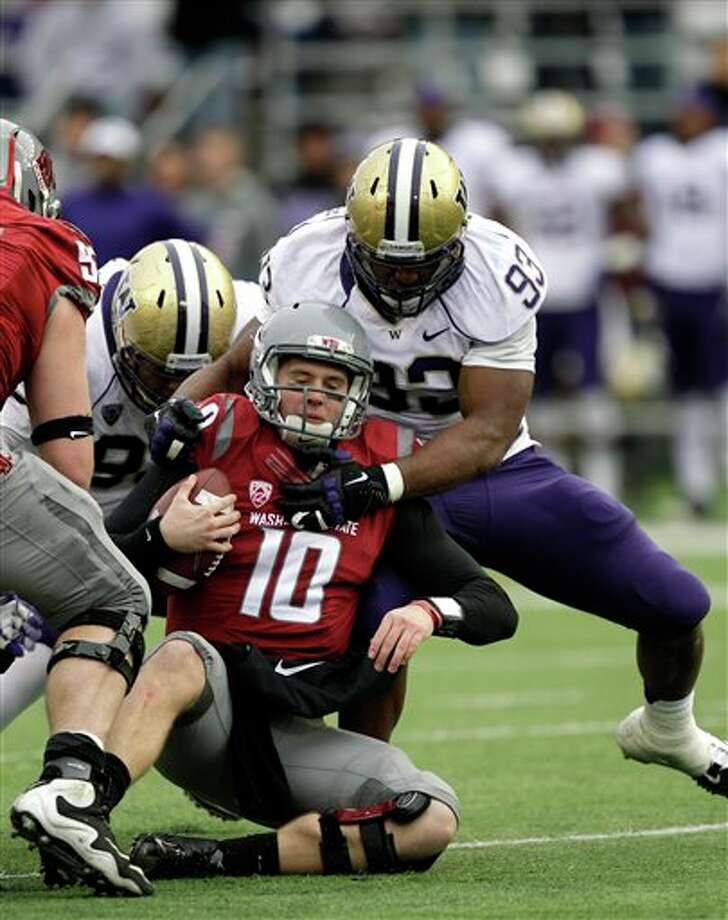 Washington State quarterback Jeff Tuel (10) is sacked by Washington's Andrew Hudson (93) in the first half. Photo: Ted S. Warren, AP / AP