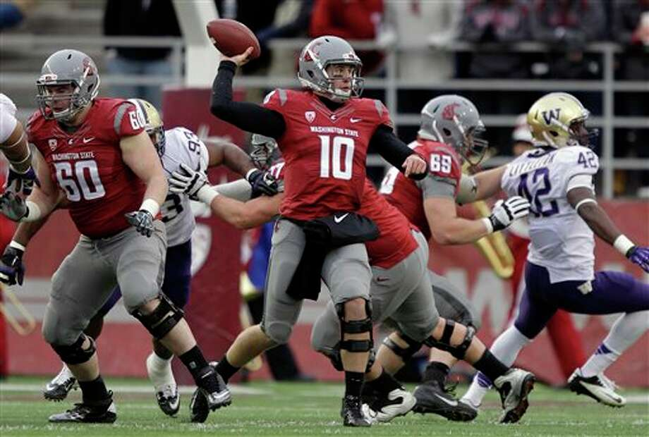 Washington State quarterback Jeff Tuel (10) looks to pass as WSU's Elliott Bosch (60) offers protection in the first half. Photo: Ted S. Warren, AP / AP
