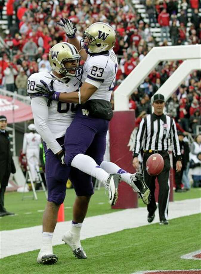 Washington's Austin Seferian-Jenkins, (88) and Kendyl Taylor (23) celebrate after Seferian-Jenkins scored a touchdown against Washington State in the first half. Photo: Ted S. Warren, AP / AP