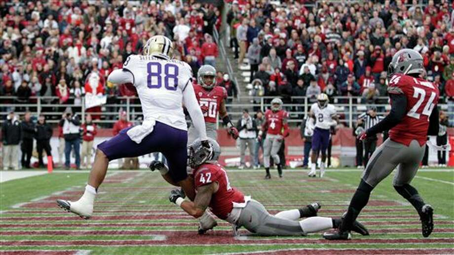 Washington's Austin Seferian-Jenkins (88) takes Washington State's Cyrus Coen (42) into the end zone with him as he scores on a touchdown reception in the first half. Photo: Ted S. Warren, AP / AP