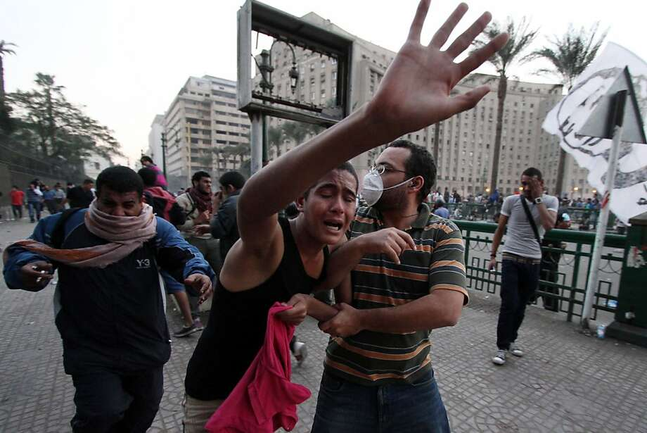 Protesters run for cover as they suffer from tear gas inhalation from canisters fired by Egyptian riot police during clashes following a demonstration against Egypt's Islamist President Mohamed Morsi in Cairo's landmark Tahrir square on November 23, 2012. Morsi has assumed temporary sweeping powers that supporters say will cut back a turbulent and seemingly endless transition to democracy, but outraged critics say he has now become a dictator. Photo: Ahmed Mahmoud, AFP/Getty Images
