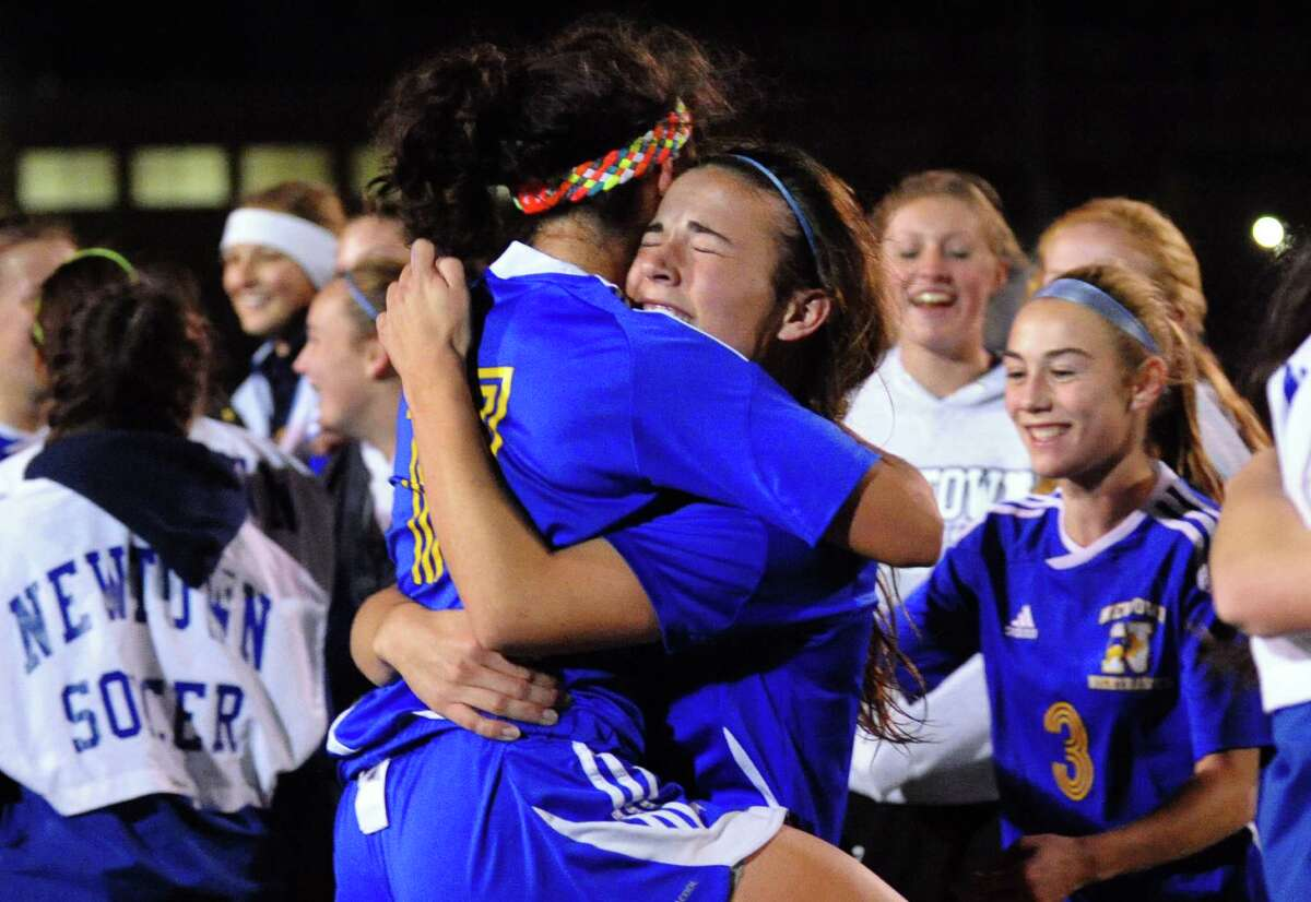 Newtown's #11 Brittany Tolla and #6 Bridget Power, facing camera, share a hug after the team defeated Glastonbury, during Class LL girls soccer championship action in West Haven, Conn. on Friday November 23, 2012.