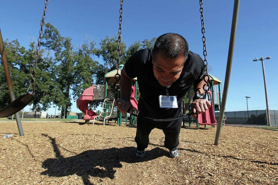 Peter Puzon with Methodist Wellness Services demonstrates a pushup exercise on the swings at Doss Park, which parents can use for a workout using playground equipment while at parks with there children Wednesday, Nov. 7, 2012, in Houston.    ( James Nielsen / Chronicle ) Photo: James Nielsen, Staff / © Houston Chronicle 2012