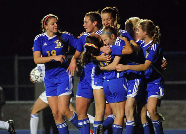 Newtown teammates surround #3 Sarah Lynch after she scored the tie breaking goal against Glastonbury, during Class LL girls soccer championship action in West Haven, Conn. on Friday November 23, 2012. Photo: Christian Abraham / Connecticut Post