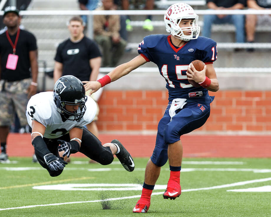Roosevelt quarteback Jacob Preciado (right) sidesteps a flying tackle by Steele's Justin Garcia during the first quarter of their Class 5A Division II second round playoff game at Heroes Stadium on Nov. 23, 2012.  Steele won the game 45-0.  MARVIN PFEIFFER/ mpfeiffer@express-news.net Photo: MARVIN PFEIFFER, Express-News / Express-News 2012