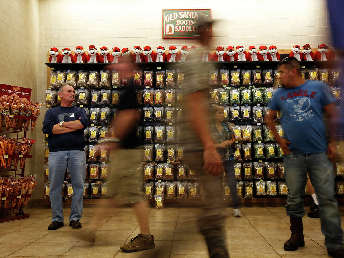 Tim Cobb, traveling from Houston to San Antonio, left, watches the crowds go by during Black Friday at Buc-ee's in Luling on Friday, Nov. 23, 2012.