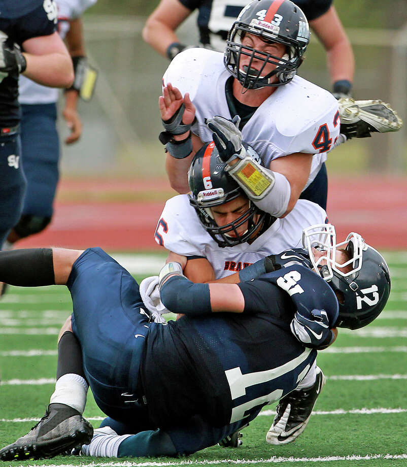 Ranger quarterback Garrett Smith is slammed down by Bronco defenders Cameron Rogers (43) and Alec Sifuentes as Brandeis beats Smithson Valley 28-20 at Camalander Stadium in second round playoff action on November 23, 2012. Photo: Tom Reel, Express-News / ©2012 San Antono Express-News