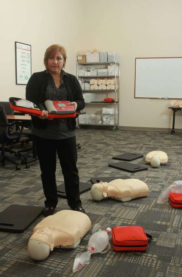 (For the Chronicle/Gary Fountain, November 7, 2012)  Linda Alferranti, a paramedic and EMS educator, in a CPR classroom with manikins used in the class on the floor. She is holding a AED (automatic external defibrillator). Photo: Gary Fountain, Freelance / Copyright 2012 Gary Fountain.