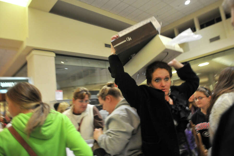 A shopper holds boxes of boots above her head as she makes her way through a crowd during Black Friday shopping at a Belk store in Oglethorpe Mall in Savannah, Ga. on Friday, Nov. 23, 2012. (AP Photo/The Morning News, Richard Burkhart) THE EXAMINER.COM OUT; SFEXAMINER.COM OUT; WASHINGTONEXAMINER.COM OUT