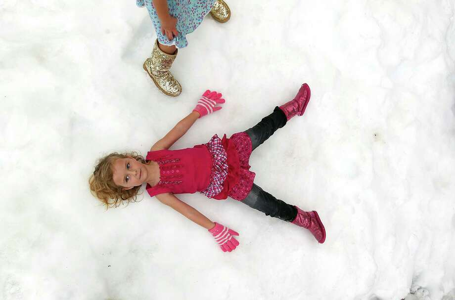 "Makenzie Davis, 4, makes a snow angel in the snow as IKEA Houston hosted a Swedish-inspired holiday experience complete with real snow, free breakfast, live reindeer and a visit from Jultomten, Sweden's Santa Claus Friday, Nov. 23, 2012, in Houston. This was the first time Makenzie had experienced snow. ""I like it cause it's cold,"" she said. Photo: Johnny Hanson, Houston Chronicle / © 2012  Houston Chronicle"